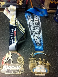 Making pimps jealous with our finisher medal swag. These things were HUGE. KS Half Marathon on left, Rock the Parkway on right.